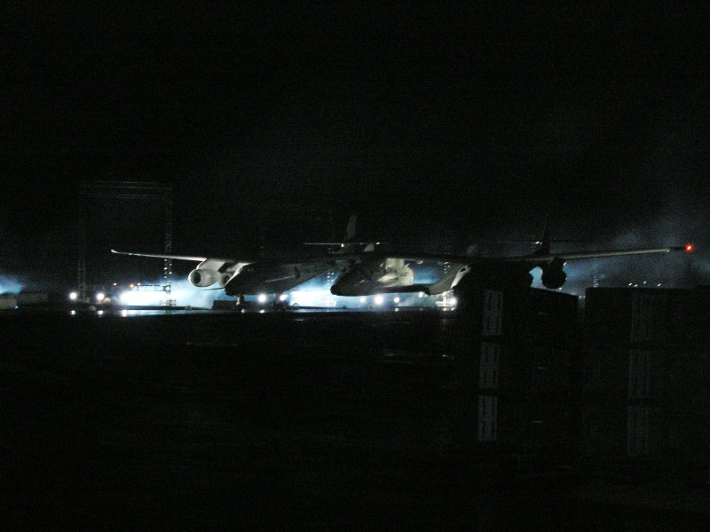 WhiteKnightTwo (WK2) taxis out from the darkness to reveal SpaceShipTwo (SS2) during the windy, frigid Mojave night.